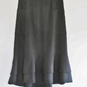 100 % NY: Lækker nederdel med flæse nederst. Længden er asymetrisk.  Materialet er 89 % bomuld + 11 % hør.   Farve: Sort Oprindelig købspris: 700 kr.   Livvidde: 75 cm Længden: 82 cm/89 cm  Ingen byt, og prisen er fast