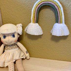 Håndlavet regnbue  Elegant regnbue som kan pynte på børneværelset, hænge på sengekanten, som en del af en billedvæg.  Viklet i bomuldsreb og med bomuldsgarn og har en fin træring til ophæng.  Højde (uden træring): 16 cm Højde (med træring): 23 cm Bredde: 14 cm