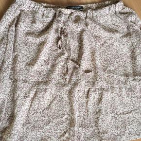 Helt ny lækker nederdel med flot mønster i beige/mørkerød.