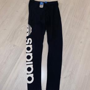 Lækre Adidas træningstights / bukser i str. UK 10/US S i helt sorte med Adidas stående ned af højre ben. Næsten ikke brugt.