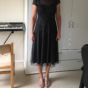 Flot gallakjole fra Vera Mont i mørkeblå/grå - perfekt til større fester/galla med de fine palietter. Kjolen er i en str. 40, og sælges til 1.250, - (er dog åben for bud). Nypris var 2.500, og kjolen er kun brugt en gang, hvorfor den er i god stand.  Sælger også stiletterne på billedet - se min anden annonce for nærmere info.