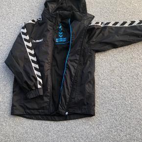 Hummel fodboldjakke i str. 12/152 i sort. Super lækker jakke med aftagelig hætte.  Prisidé dkk 125,00 - kom gerne med et seriøst bud :-)  Forsendelse med DAO dkk 36,95.