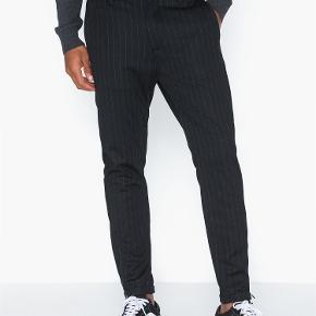 Gabba Pinstripe chino i en sort farve. Buksen har lynlås detalje ved benet. Buksen er udstyret med to sidelommer og to baglommer. Lukkes med topknap og skjult lynlås. Kvalitet: 48% viskose, 47% polyester, 5% elastan.  Style: Pisa Chino Pinestripe B