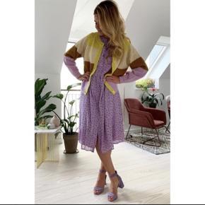 Lollys Laundry kjole, der i sandhed er så smuk, at den vil blive din favorit, kjolen kommer i en lyselilla farve med små, fine blomster i en lys orange og lilla farve.  Kjolen har korte ærmer, knapper langs forsiden og pasformen er løs med skæring i taljen. Kjolen har en tynd foring. Ydre: 100% polyester  For: 100% viskose Str. XS, men en løs kjole så en str. S + lille M vil også kunne passe den, kjolen er helt ny Stadig med mærke på.