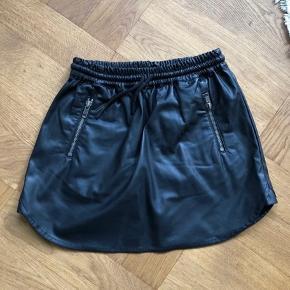Lækker nederdel i kunstlæder med lynlås-lommer i taljen. Brugt få gange. Lidt stor i størrelsen.