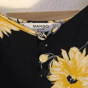 Basic mørkeblå kjole med gule og hvide blomster og tynde stropper fra Mango. Den er blevet brugt men sjældent, og bærer ikke yderligere præg af det, end strygetur ville dog ikke skade.