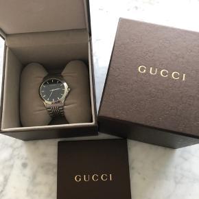Sælger dette Gucci G timeless ur med sort Skive.  Reference ne. YA126402. Købt i februar 2014. Næsten ikke brugt. Garanti, æske, mærke og ekstra led fælger med.