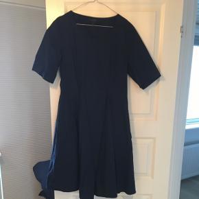 50'er inspireret navyblå kjole fra Cos. Giver flot talje og fine læg der sikrer flot fald i kjolen.   Knælang (jeg er 170cm)  Byd!