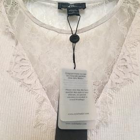 Aldrig brugt og stadig med tags. En XL, men Pga. ribben er  den ikke meget stor i str. Min mor er en dk 38 40 M L og passer den. Længde: 70 cm fra nakken og ned. 70% silke og 30% cotton. Farven hedder Pearl. Søgeord: top silke rib lace undertrøje blonde blonder silk Pearl lang silk