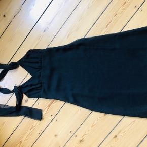 Super sød sort kjole, der hænger flot til kroppen. Fine detaljer - bånd der kan bindes på flere måder eventuelt omkring halsen. Brugt 1 gang til bryllup