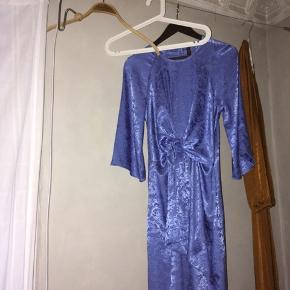Lang kjole i lyseblålatin, med binde detalje i taljen. Brugt en gang til nytår, har ingen fejl 🌊