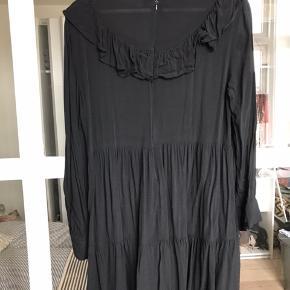 Kjole med flæsekant, lynlås i nakken.  Jeg har brugt den med stramme jeans under.  Den går mig til midt på låret. (173 cm høj). Der står large i den men den svarer til en s/m. Køber betaler Porto.