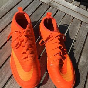 Smarte indendørs sko/sportssko fra Nike i flot orange nuancer. Ikke brugt meget - se billede af sålen, men nogen slid i farven ovenpå skoen.  Størrelse 43 = UK 8,5 = 27,5 cm Portoen er 38 kr. som køber betaler.  Bytter ikke. Se også mine øvrige annoncer. Betaling via mobilepay og sender med DAO fra dag til dag. (10)