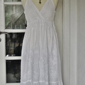 """100 % NY kjole med tag. Kjolen er af mrk. Indian Imperium. Flot hvid bomuldskjole med blonde under brystet og blomster-broderi på nederdelen i hvid i hvid. Nederdelen er i 2 lag, så den er ikke gennemsigtig. Ryggen af kjolen er med elastik, så målene er flexible.  Størrelsen hedder """"One Size"""", men se målene nedenfor.  Brystvidde: 48-55 cm x 2 pga elastik-ryggen Livvidde: 40-50 cm x 2 pga elastik i ryggen Længde: 103 cm"""