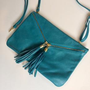 Lædertaske i flot blå farve købt i Firenze. Indvendigt har den en lynlåslomme. Den har en lang crossbody-rem, som kan justeres i længden, og der medfølger også en kort rem, så tasken kan bruges som clutch. Både den lange og den korte rem kan nemt på- og afmonteres tasken.  Aldrig brugt. Mål: 18x28 cm.