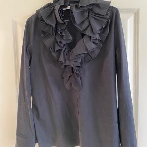 Sort skjorte med detaljer ved kraven.  Str. M Ingen spor af brug - skjorten er brugt er par gange. Kan vaskes i maskinen.  Materialet har lidt strech.  Kan passe en størrelse 38-40.