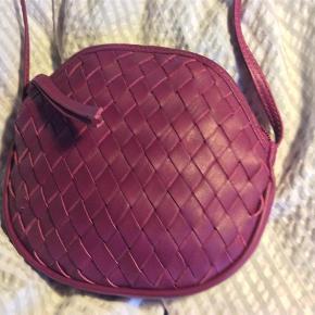 Varetype: Lille skuldertaske Størrelse: Ca 16 cm Farve: Lilla  Sød lille rund taske med lang rem. Foret. Aner ikke om det er læder?