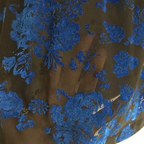 Brugt få gange - det er blå velour blomster på sort gennemsigtig stof. Super smuk bluse. Passer en small/medium ☺️