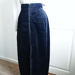 En alt for skøn vintage nederdel i fløjl, med sølv nålestriber og hægtelukning. Billederne er lysnet så man kan fornemme striberne, ellers fremstår den i perfekt stand uden tegn på slid i en støvet sort farve. Længde 80, talje 72.