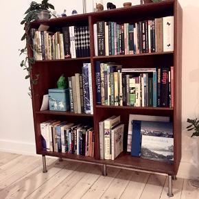 Flot reol i mørkt træ - måske teak eller noget der ligner. Har selv sat ben på, hvilket gør møblet let at se på, selvom det er fyldt med tunge bøger.  Mål i cm b: 114,5 d: 31 h: 108  Kan afhentes på Østerbro.