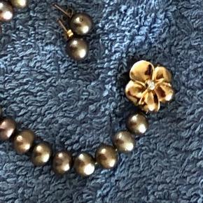 Smykkelås, blomst med en diamant i midten 14 karat guld. Smykket er fra Aagaard, Connection. Der medfølger ægte perlekæde og øreringe - bronchefarvede - købt på Isla Margarita. Dutternrne på perlekæden er monteret hos guldsmed i Århus. Guldsmeden laver til alle slags kæder . Perlekædens længde er 43 cm. Brugt 8-10 gange.  Porto betales af køber - eller afhentes .