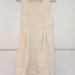 Smuk, romantisk kjole fra H&M. Kjole er i tyk kvalitet og er figursyet med smukke blonder / hæklet / crochet stof over hele kjolen. Kjolen er med v-neck og hvid / råhvid.
