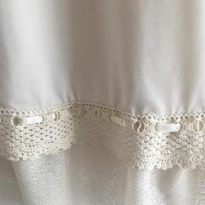 Sæd og romantisk kjole med hæklet blondekant forneden.   Andet Farve: Creme