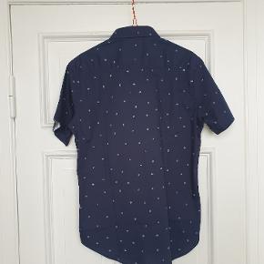 Kortærmet skjorte fra Level Ten, købt i Brooklyn som gave. Aldrig brugt. Sælges billigt pga. en enkelt LILLE ujævnhed i materialet (se forstørret detaljebillede).