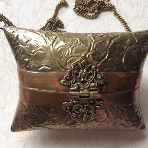 En helt unik lille taske i metal. Metallets art kan jeg ikke afgøre, men den har en kobberkant.