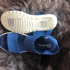 SÆLGES FOR 100 kr. + 35 kr. til DAO PORTO - VED HANDEL VIA MOBILE PAY. Str. 38. Overdel i blå elastisk materiale. Semiplateausål og kilehæl. Hæl slingback strop så sandalen sidder perfekt på foden. Memory Foam. Stødabsorberende mellemsål, som at gå på en yogamåtte. Hælhøjde ca. 6 cm. Ikke brugt meget. Nypris 800 kr. Bytter ikke. Jeg rydder op og sælger billigt.