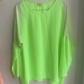 Neongrøn bluse med detaljer i silke. Den har en slids i ryggen.