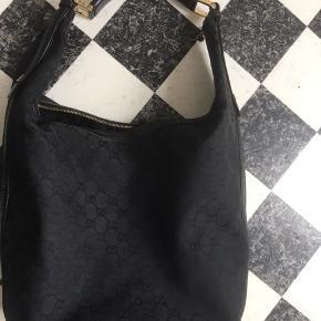 """Flot rummelig skuldertaske fra Gucci i sort monogram.   Tasken er godt brugt og har brugsspor i bl.a.  folderne (ses dog ikke så meget under brug, kun når de """"foldes ud"""") læder i flot stand og næsten som ny indvendig.   Kan ses i Kolding eller sendes mod betaling af fragt med Dao for 45kr.   Yderligere billeder kan tilsendes."""