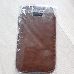 Nyt universelt etui til telefon i kunstlæder. Telefonen sættes ind i det, som i lomme, og trækkes op ved hjælp af snoren på bagsiden af etuiet. Den var købt til Samsung S3, men passer til andre telefoner med max mål 13,5×6,5×0,8 cm.