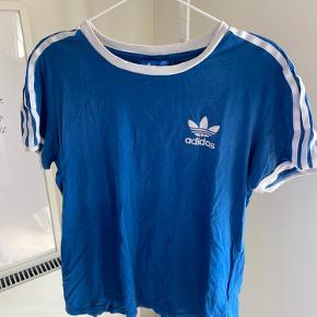 Cool Adidas t-shirt i flot blå farve. Det er en str 38, men giver oversized look på en str xs-s. T-shirtet er vasket en del gange, hvilket man også kan se lidt i farven