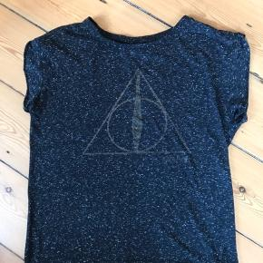 Harry Potter T-shirt. Sort med hvide nister. Det er en str 12 (engelske str) hvilket svare til str 40 Har en del fandom T-shirts til salg. Fra ikke rygerhjem #30dayssellout