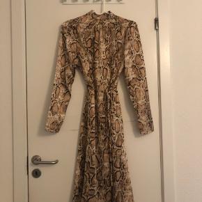 """Smuk """"snake"""" kjole i noget stof som minder om satin. Den er helt ny og aldrig brugt, kun prøvet på. Stadig prismærke.  Det er en str 38 men fitter en 34-36. Sælges fordi den er for lille til mig."""