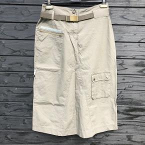 Smart nederdel fra Share med flotte detaljer.   Er næsten sikker på, at det er 100% bomuld - men der er ikke noget mærke i.   Bæltet følger naturligvis med :-)  Livvidde: 78 cm Længde: 78 cm  Sender gerne med DAO, men du kan også hente selv kontaktfri med mobilepay😊