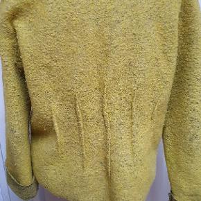 Den er mærket str 46 men virker mindre. Materialet er 67%uld, 33% polyester