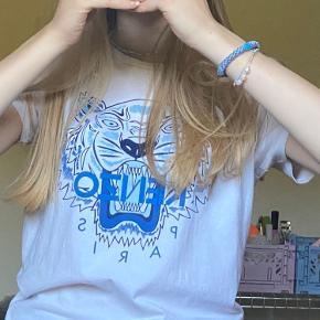 """Brugt få gange. OBS: rigitg børnestr. Da den er stor i str har jeg valgt at sætte den til en str S. Er 167 høj.   T-shirt fra Kenzo Flot Kenzo t-shirt i hvid med et stort print på fronten af en brølende tiger i navy og lyseblå. Henover samt under tigeren står der """"Kenzo Paris"""" med blå bogstaver. Kenzo t-shirten har korte ærmer og en smal ribkant omkring halsen. Fremstillet af: - 100% bomuld Model: Tiger JB Per 1, Style: KN10738, Farve: Optic White"""