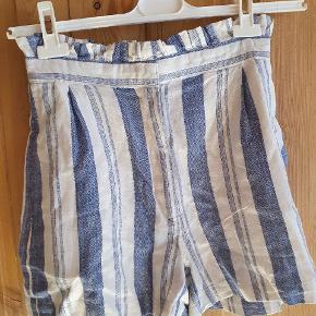 Super fine højtaljede shorts fra Pull and Bear med hvid og blå striber. Måler 71 cm i taljen og er uden stretch. De er en størrelse M, men vil passe en str. XS/S eller 36, da de er små i størrelsen.  53% hør/linen 47% bomuld
