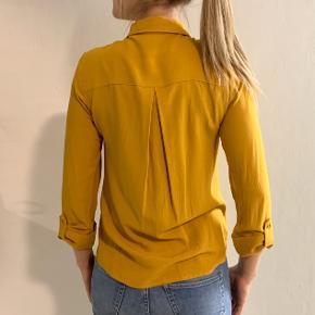 Karrygul skjorte str. XS. Brugt 1 gang - Er som ny. Ingen pletter eller tegn på slid.  Kan sendes med DAO på købers regning.