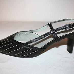 Slingbacks i sort skind med hvide stikninger. Der står størrelse 5 i stiletterne - de svarer til en 38.