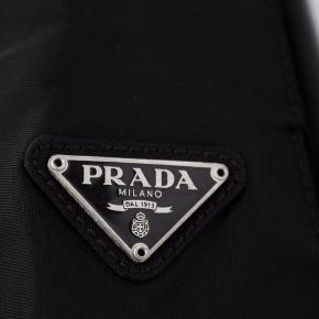 🔥🔥Prada Nylon Shoulder Bag with Silver Handle 🔥🔥  Kan hentes i Nordvest eller leveres/sendes  The iconic Prada nylon bag in black with a silver metal shoulder strap, features one inner ziplock pocket, three inner compartments, silver inscribed hardware & monogrammed lining.   - Line: PRADA - Made In Italy - Estimated Year of Design: 1990's  Details:  - Three Inner Compartments - One Inner Zip Lock Pocket - Monogrammed Lining - Silver Inscribed Hardware  Measurements:  - Hight 23cm - Width 32cm - Depth 8cm - Strap 54cm