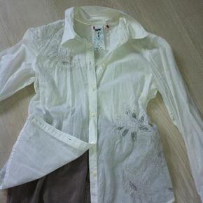 Varetype: Yndig og feminin skjorte / bluse / tunika Farve: Hvid Prisen angivet er inklusiv forsendelse.  Rigtig fin og feminin skjorte med perler og broderi.  Standen er faktisk så god som ny, - men den trænger til et strygejern :)  Brystvidde: ca. 2 x 50 cm.