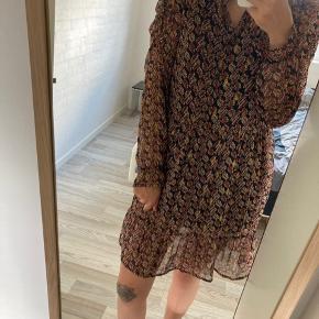 """Kjole i det fineste mønster, har detalje på ærmerne så de """"puffer"""" let. Længde er ca til knæ. Der medfølger en sort underkjole med. Kun brugt 2 gange."""