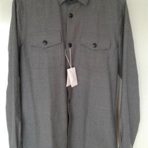 Varetype: Mænd skjorter Farve: Grå Oprindelig købspris: 1000 kr. Prisen angivet er inklusiv forsendelse.  Super lækker skjorte fra Samsøe & Samsøe . Ubrugt med tags.  Skjorten er lavet i en suveræn kvalitet 70 % uld 30 % Polyester.  Kraftig i kvaliteten.   Sendes med DAO uden omdeling ( forsikret forsendelse )  MOBILEPAY foretrækkes.  Kan afhentes i Rødovre.