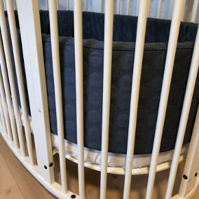 Stokke junior seng af ældre dato. Der er lidt slid på kanterne - se billede. Kan nemt males hvis det ønskes. Der medfølger kit til baby sengen, sengehimmel (der er dog et lille hul i stoffet nederst. Man ser det ikke meget når den står og det kan nok godt sys. Har jeg ikke forsøgt. Der medfølger madrasser til prisen hvis det ønskes. Enkelte af de originale skruer er blevet væk, hvorfor der skal monteres en anden, hvis man samler babysengen. Vi har en der passer til, som følger med. Skal afhentes nær Tønder. Sengeranden er fra smallstuff og er aldrig brugt. Den er altså helt som ny. Den er gråblå. Kan tilkøbes for +250 kr - nypris på sengeranden ligger på 500-700 kr. Pris for sengen 500 kr. nypris for bare juniorsengen er over 4000. Dertil skal købes baby madras og sengehimmel. Så den sælges billigt :)