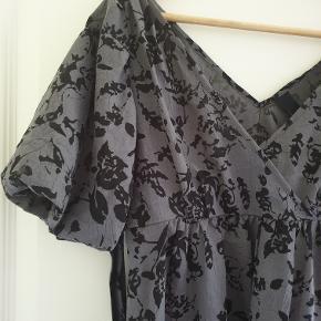 Fin blusekjole / lang bluse i grå med sort blomstermønster og puf-ærmer. Størrelse 34 / x-small Kjolen lukkes med lynlås i siden og bindes omkring livet. Fra dyrefrit og røgfrit hjem. Kjolen kan hentes i Ebeltoft, hvor jeg bor, eller hentes i forbindelse med mit arbejde i Brabrand, Århus. Jeg sender også gerne. Kom gerne med et bud! :)