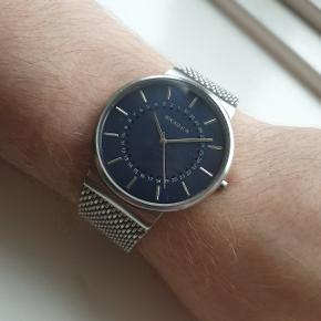 Lækkert ur med blå skive herreur / herre ur fra Skagen - modellen hedder Ancher og SKW6234 er modelnummeret. Der er enkelte skrammer på, men som ses på billederne, så er de ikke rigtig synlige, når man har det på. Sælges da min kæreste ikke får det brugt. Nypris var ca. 1800 kr - sælges for 850 kr eller giv et bud.  Kan hentes på Amagerbro, vi kan mødes og handle, eller det kan sendes med posten.