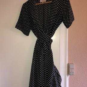 Fin slå-om kjole fra Lollys. Sort med hvide prikker.  Den er fra sidste sæson og kun brugt få gange.